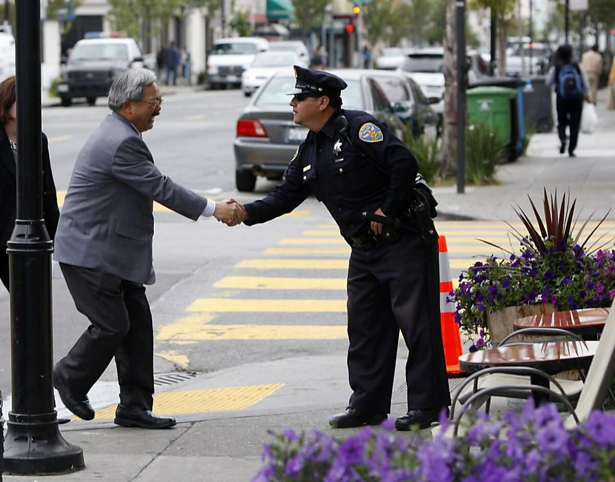Mayor Ed Lee (l to r) shakes the hand of SFPD Officer Percy Hernandez as he arrives at North East Medical Services before the launch of a permanent Community Ambassadors Program following a year-long pilot on Monday, August 1, 2011 in San Francisco, Calif.