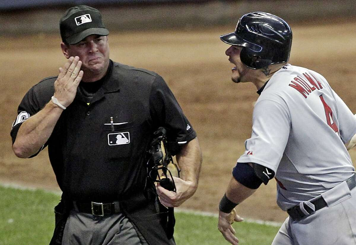 St. Louis Cardinals' Yadier Molina argues with home plate umpire Rob Drake after being called out on strikes during the 10th inning of a baseball game against the Milwaukee Brewers Tuesday, Aug. 2, 2011, in Milwaukee.
