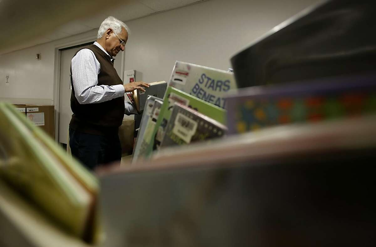 Saeed Malik looks through the donated books at the Main Library in San Francisco, Ca. on Thursday August 4, 2011. Saeed Malik a former U.N. official on a trip to San Francisco saw the public library's bookmobile traveling around town which inspired him to launch his own bookmobile in his country of Pakistan. With the help of the library's manager of mobile outreach, Katrin Reimuller, 422 books were donated to Malik's program.