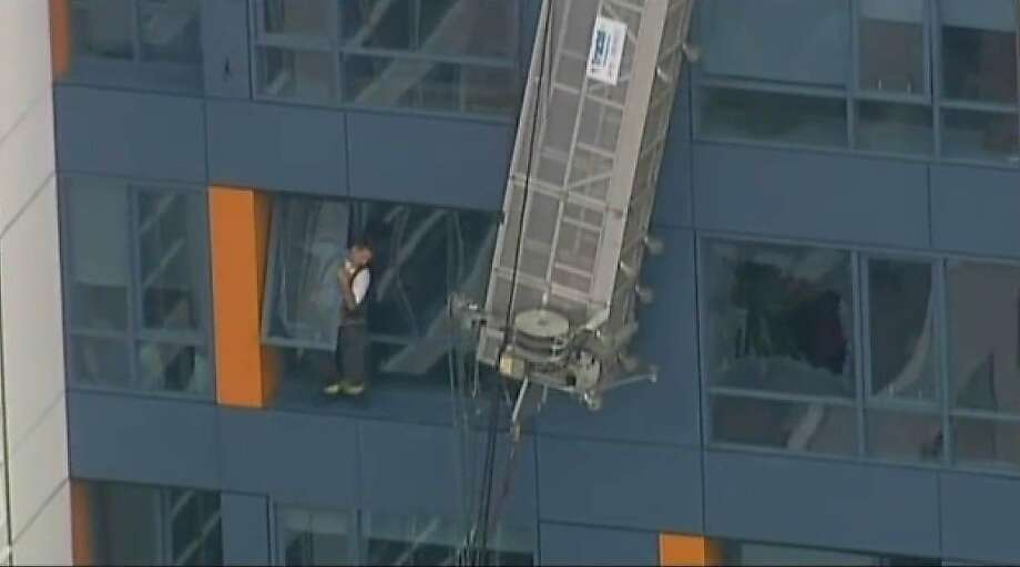Two window washers were rescued this morning after their scaffolding broke and left them dangling outside a high-rise condominium building in San Francisco's Mission Bay. Photo: Cbs 5