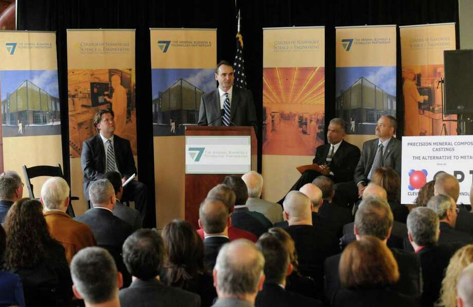 Panos Angeloppolos, president of Cleveland Polymer Technologies, center speaks during a press conference to announce his company moving their headquarters and expanding operations at the Watervliet Arsenal in Watervliet, NY Wednesday, Nov.30, 2011.( Michael P. Farrell/Times Union) Photo: Michael P. Farrell
