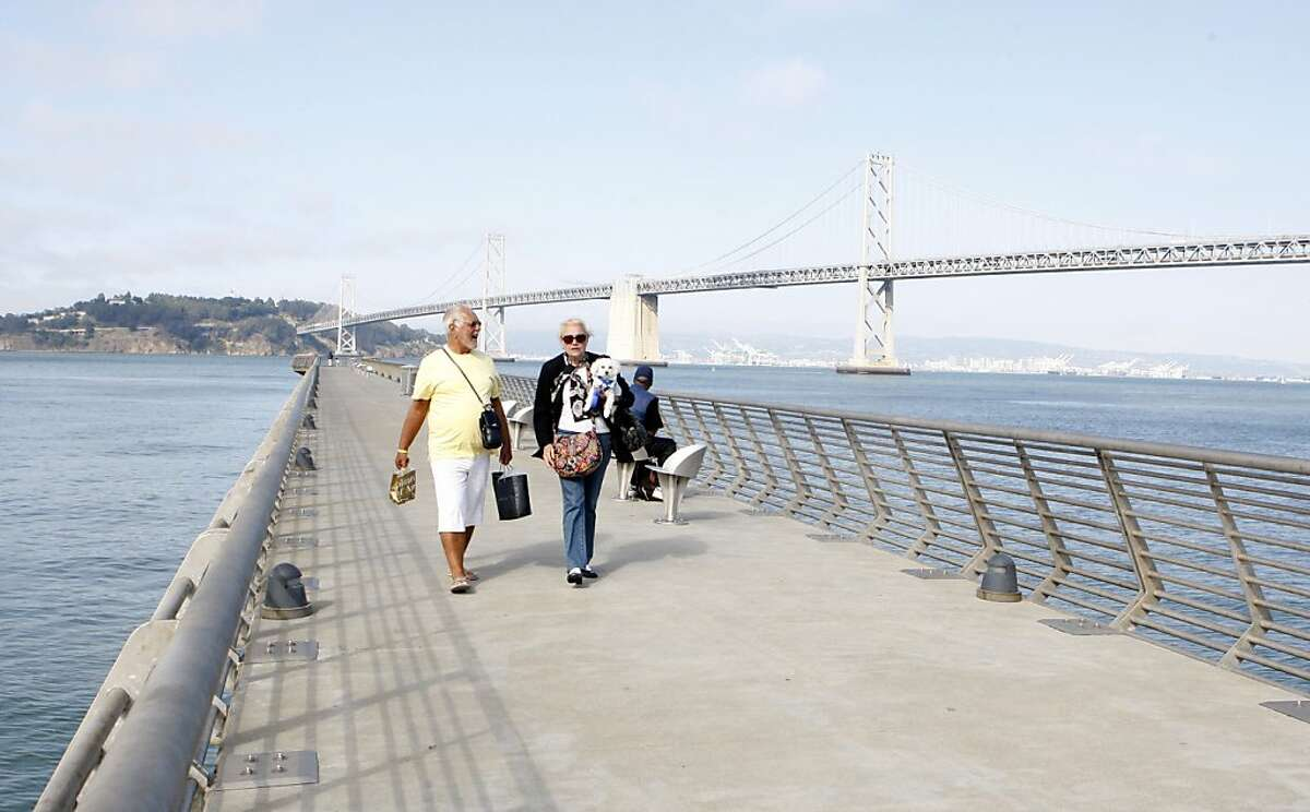 A couple enjoys a stroll down Pier 14 on the Embarcadero promenade on Friday, July 31, 2011 in San Francisco, Calif.