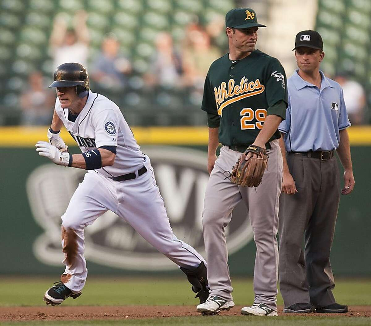 With the Oakland Athletics' attention elsewhere, Seattle Mariners baserunner Brendan Ryan, left, spots an opportunity to advance a base in the first inning on Tuesday, August 2, 2011, at Safeco Field in Seattle, Washington.