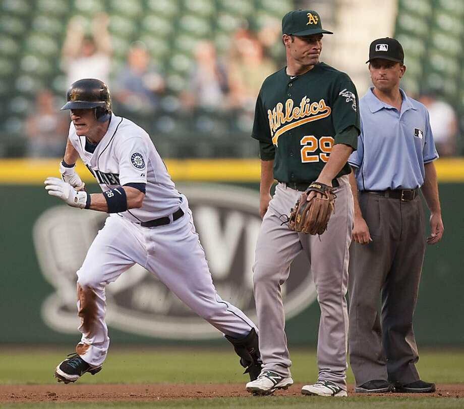 With the Oakland Athletics' attention elsewhere, Seattle Mariners baserunner Brendan Ryan, left, spots an opportunity to advance a base in the first inning on Tuesday, August 2, 2011, at Safeco Field in Seattle, Washington. Photo: Dean Rutz, MCT