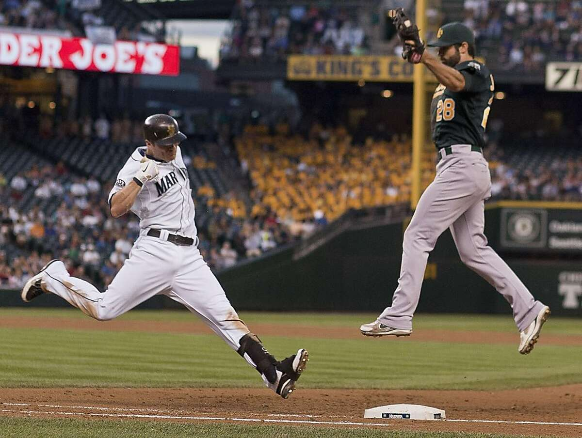 An errant throw to Oakland Athletics first baseman Conor Jackson, right, by pitcher Rich Harden allows the Seattle Mariners' Brendan Ryan, left, to safely reach base in the fifth inning on Tuesday, August 2, 2011, at Safeco Field in Seattle, Washington.