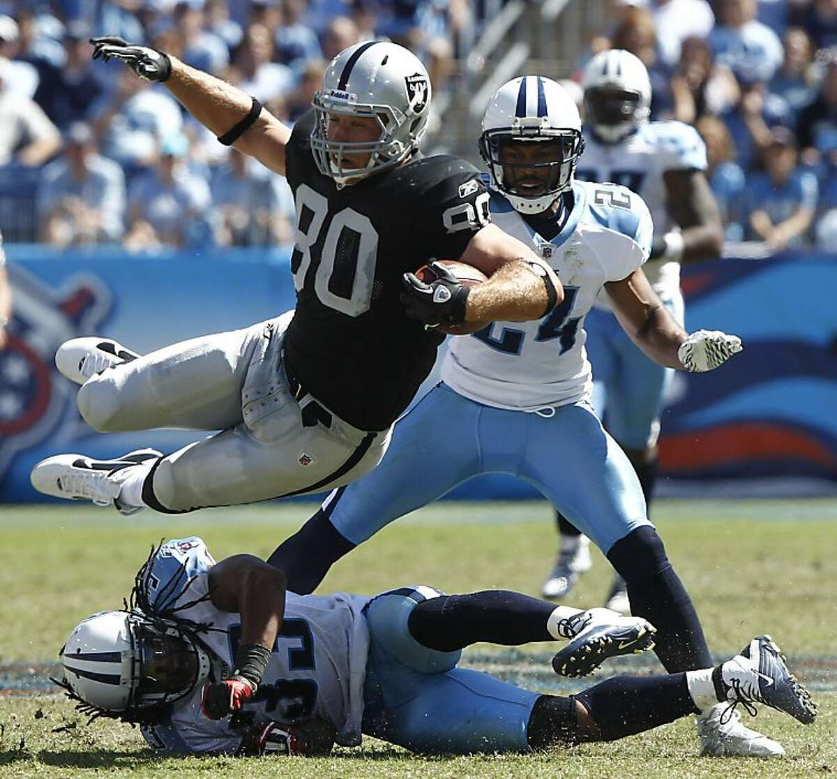Oakland Raiders tight end Zach Miller (80) is upended by Tennessee Titans defender Michael Griffin (33) in the second half of their NFL football game at LP Field in Nashville, Tenn., Sunday, Sept. 12, 2010.
