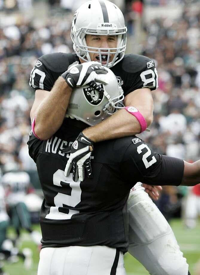 Oakland Raiders tight end Zach Miller, top, jumps in the arms of teammate JaMarcus Russell after Miller's 86-yard touchdown reception against the Philadelphia Eagles in the first quarter of an NFL football game in Oakland, Calif., Sunday, Oct. 18, 2009.  (AP Photo/Paul Sakuma) Photo: Paul Sakuma, AP
