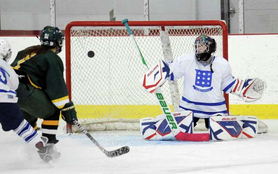 At left, Pam Schulman # 7 of Greenwich Academy shoots high and to the left as Portledge School goalie Emily Appenzeller covers the net during Girls high school ice hockey game between Portlegde and Greenwich Academy at Hamill Rink in Byram Wednesday night Nov. 30, 2011. Photo: Bob Luckey / Greenwich Time