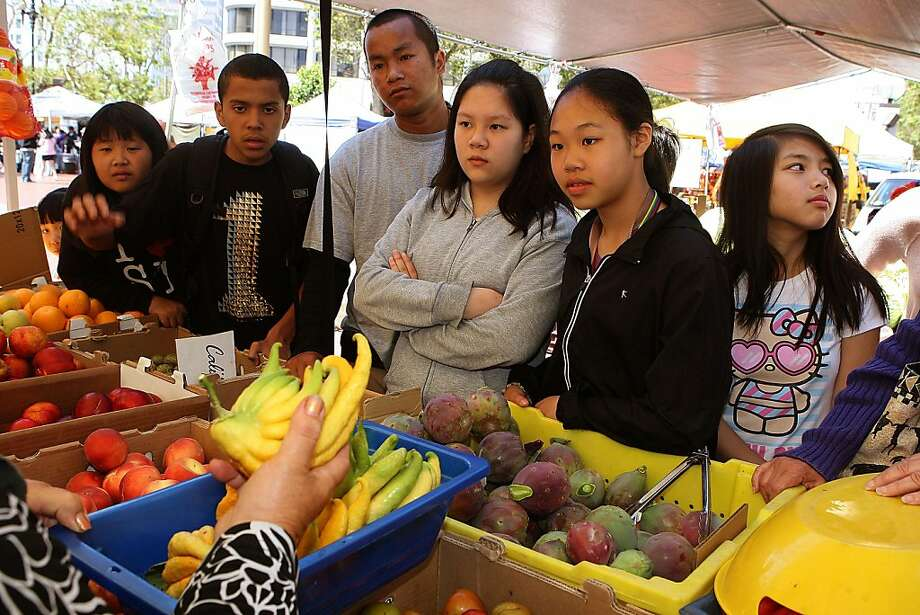Left to right--Joline Chang, 12 years old, Abner Mejia, 14 years old, Sammy Soun of the Boys & Girls club, Wendy Cha, 12 years old, Joey Tran, 11 years old, Mayna Ha, 12 years old, from the Boys &Girls  club in the Tenderloin being shown the Buddha's Hand citron fruitby Rosa De'Santis at the Heart of the City farmers market in the U.N. Plaza in San Francisco, Calif., on Wednesday, July 27, 2011.  The Heart of the City Farmers Market is celebrating its 30th anniversary with a campaign to educate local kids living in the Tenderloin and Civic Center  about eating healthy. Photo: Liz Hafalia, The Chronicle