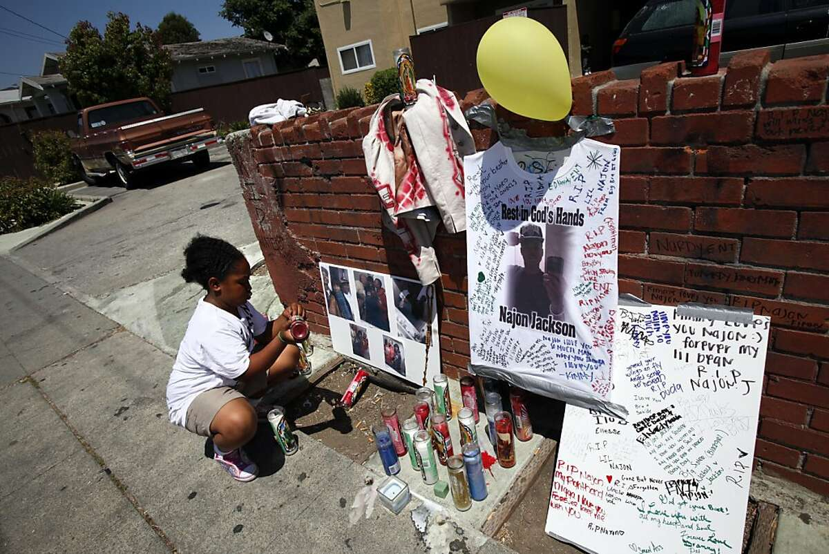Sah-de Jackson, 10, straightens the memorial to her brother, Najon Jackson, 16, outside her grandmother's apartment in Oakland, Calif., Monday, August 1, 2011. Najon Jackson was shot and killed outside the apartment Saturday night.