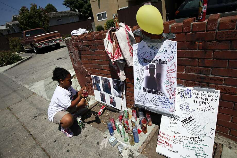 Sah-de Jackson, 10, straightens the memorial to her brother, Najon Jackson, 16, outside her grandmother's apartment in Oakland, Calif., Monday, August 1, 2011.  Najon Jackson was shot and killed outside the apartment Saturday night. Photo: Sarah Rice, Special To The Chronicle