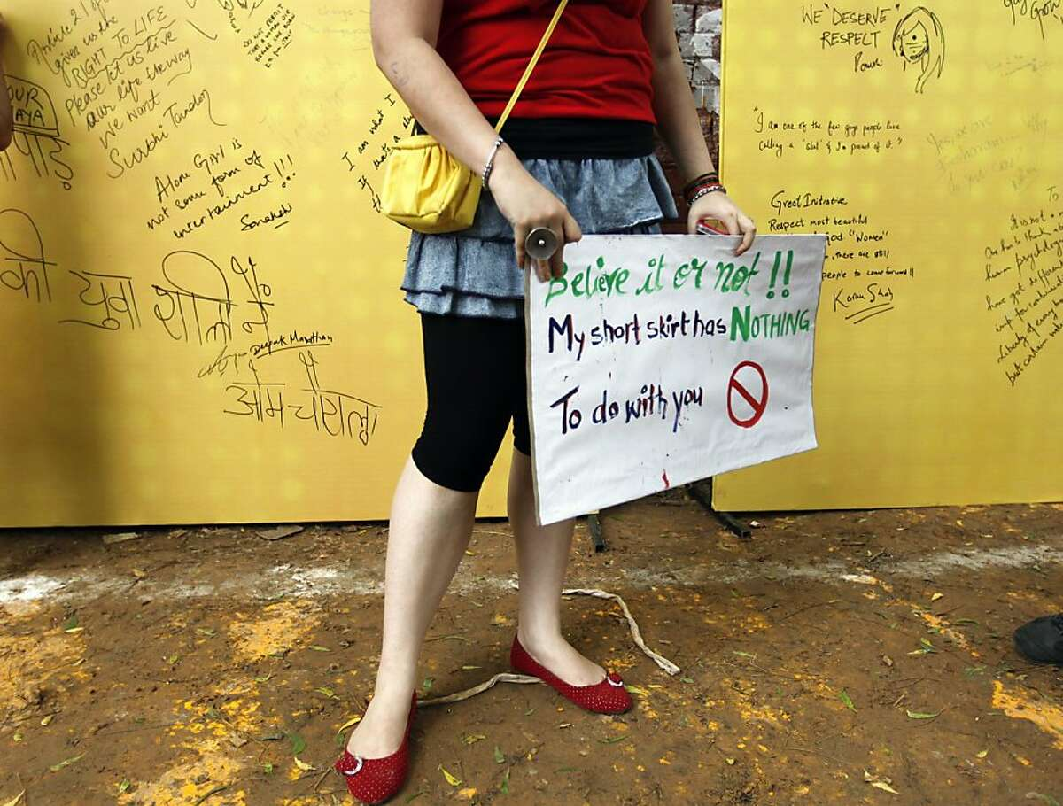 """A woman holds a placard as messages written by people are seen in the background at the Delhi """"SlutWalk"""" in New Delhi, India, Sunday, July 31, 2011. There were no short skirts, fishnet stockings or lingerie on display that were the staple of other global""""SlutWalk"""" marches as hundreds gathered in India's capital on Sunday to protest sexual violence against women.The event condemned the notion widely held in this traditional society that a woman's appearance can explain or excuse rape and sexual harassment. In India, public sexual taunting or even groping of women, locally known as """"Eve teasing"""", is common."""