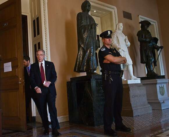 US Senate Majority Leader Harry Reid leaves a meeting of Democratic senators to speak to the press at the Capitol in Washington,DC on August 1, 2011. The fate of a massive US austerity plan headed into the hands of Congress, where leaders have just hoursto win over skeptical lawmakers or face an unprecedented debt default. President Barack Obama late Sunday unveiled a package of more than 2.4 trillion USD in spending cuts over the next decade and said it enjoyed the support of lawmakers from both parties, cheering anxious global markets. Photo: Nicholas Kamm, AFP/Getty Images