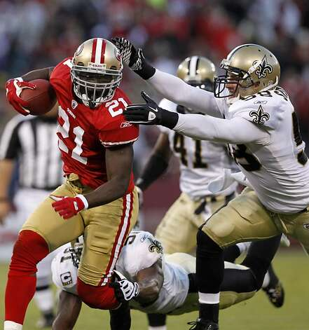Frank Gore eludes Scott Shanie during the San Francisco 49ers and New Orleans Saints game at Candlestick Park in San Francisco on Monday. Photo: Paul Chinn, The Chronicle