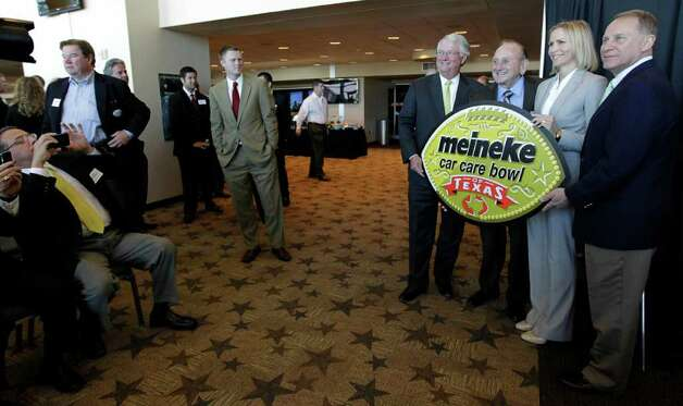 Onlookers take photos of (l-r)  Ken Walker, Chairman and CEO of Meineke Car Care, along with Sam Meineke, founder, unveil the new Meineke Car Care Bowl of Texas logo with Texas Bowl Executive Director Heather Houston, and Pete Derzis, with ERT, during the press conference to announce that ESPN Regional Television (ERT), Inc., a subsidiary of ESPN, and Meineke Car Care Centers signed a three year title sponsorship deal for the Texas Bowl, at Reliant Stadium, Tuesday, April 12, 2011, in Houston.   The annual game will match up the Big 12 versus the Big Ten, and 2011 will be the first year of the deal. Photo: Karen Warren, Houston Chronicle / Houston Chronicle