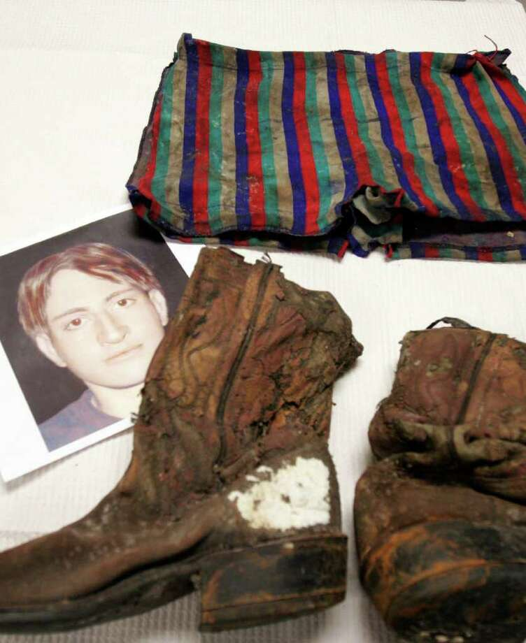 A moldy pair of cowboy boots and a pair of swim trunks found with a body nearly 34 years ago are laid out at the medical examiner's office Monday, May 12, 2008 in Houston along with a digital  image of what the victim may have looked like. The young man is one of three victims of serial killers Dean Corll and Elmer Wayne Henley who was never identified. (AP Photo/Pat Sullivan) Photo: Pat Sullivan, ASSOCIATED PRESS / AP2008
