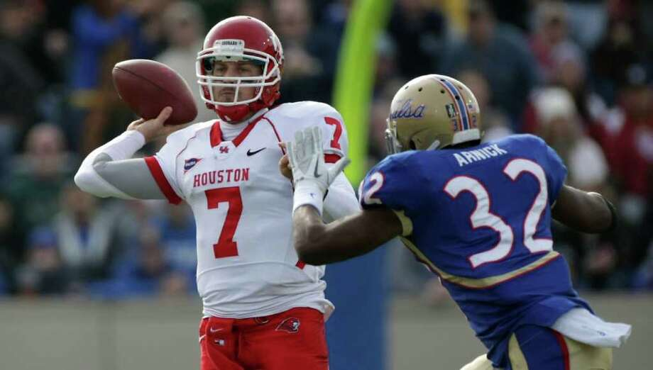 University of Houston quarterback Case Keenum (7) rolls out to avoid University of Tulsa linebacker Curnelius Arnick (32) and complete a pass during the second quarter of a NCAA football game, Friday, Nov. 25, 2011, in H.A. Chapman Stadium in Tulsa. ( Nick de la Torre / Houston Chronicle ) Photo: Nick De La Torre / © 2011  Houston Chronicle