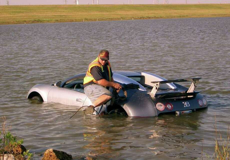 Gilbert Harrison with MCH Towing attaches a towing cable to a Bugatti Veyron that was driven into the water near Omega Bay in La Marque, Texas, on Wednesday, Nov. 11, 2009. A man blamed  a low-flying pelican and a dropped cell phone for his veering his million-dollar sports car off a road and into a salt marsh near Galveston. (AP Photo/The Galveston County Daily News, Chris Paschenko) Photo: Chris Paschenko, AP / The Galveston County Daily News