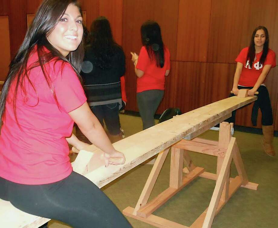 Sacred Heart University student Cassandra Nuovo, of Chi Omega sorority, see-saws with Katie Albulescu, a Kappa Phi sorority member, during a 24-hour see-saw marathon Wednesday night at SHU. Photo: Mike Lauterborn / Fairfield Citizen contributed