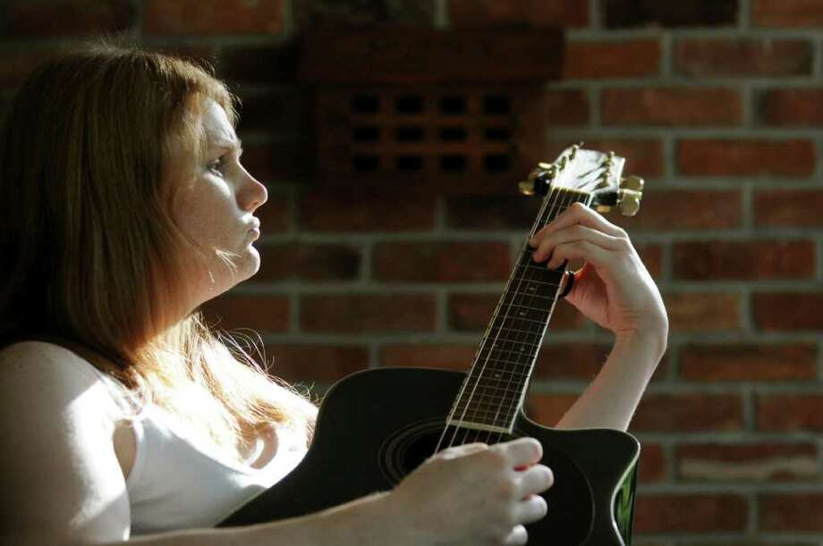 Drew Cordes strums the guitar on Tuesday, June 21, 2011, at her parents' home in Glens Falls, N.Y. (Cindy Schultz / Times Union) Photo: Cindy Schultz, Albany Times Union