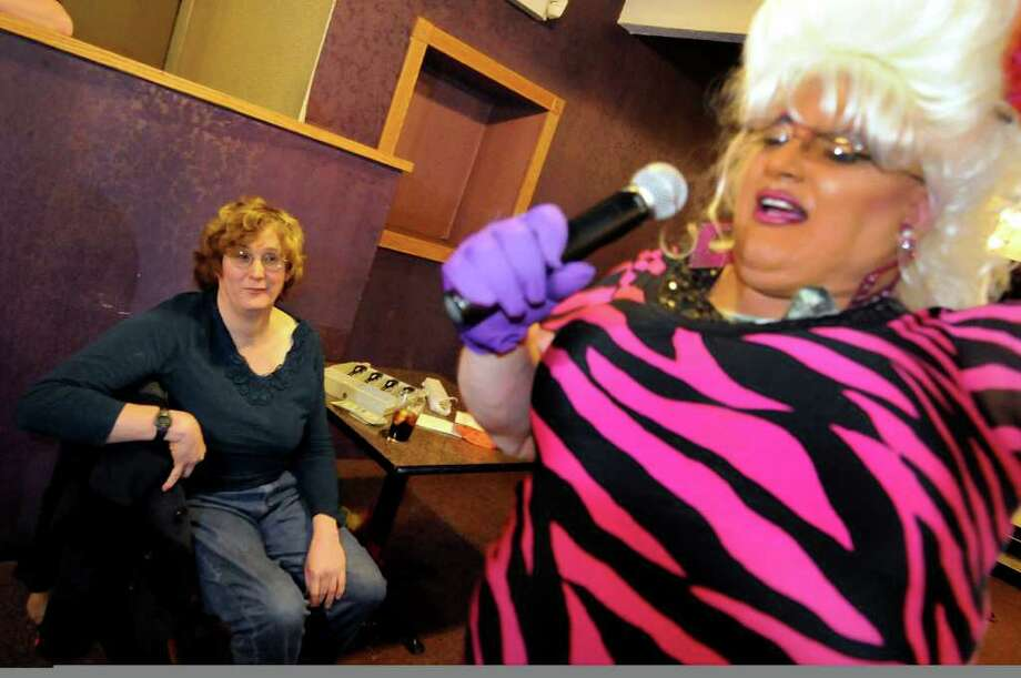 Transgender woman Robin Muse of Albany, left, who's in charge of selling tickets for the drag show, watches housemate Frieda Munchon perform on Sunday, Nov. 6, 2011, at the Irish Mist in Troy, N.Y. (Cindy Schultz / Times Union) Photo: Cindy Schultz, Albany Times Union