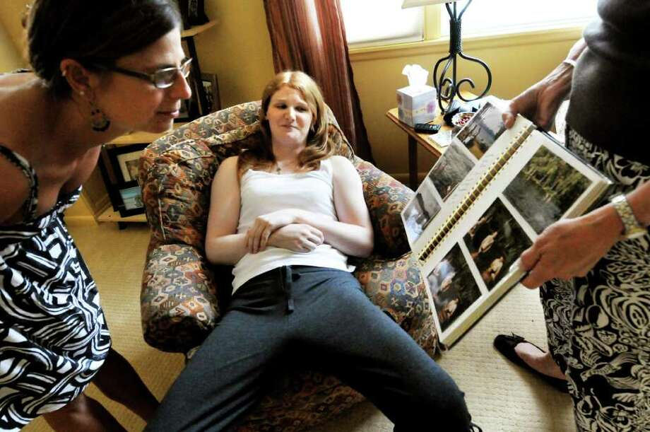 Drew Cordes, center, watches with amusement as her mother, Janet, right, shows an old photo album to her friend Melissa Mangino on Tuesday, June 21, 2011, at her parents' home in Glens Falls, N.Y. (Cindy Schultz / Times Union) Photo: Cindy Schultz, Albany Times Union
