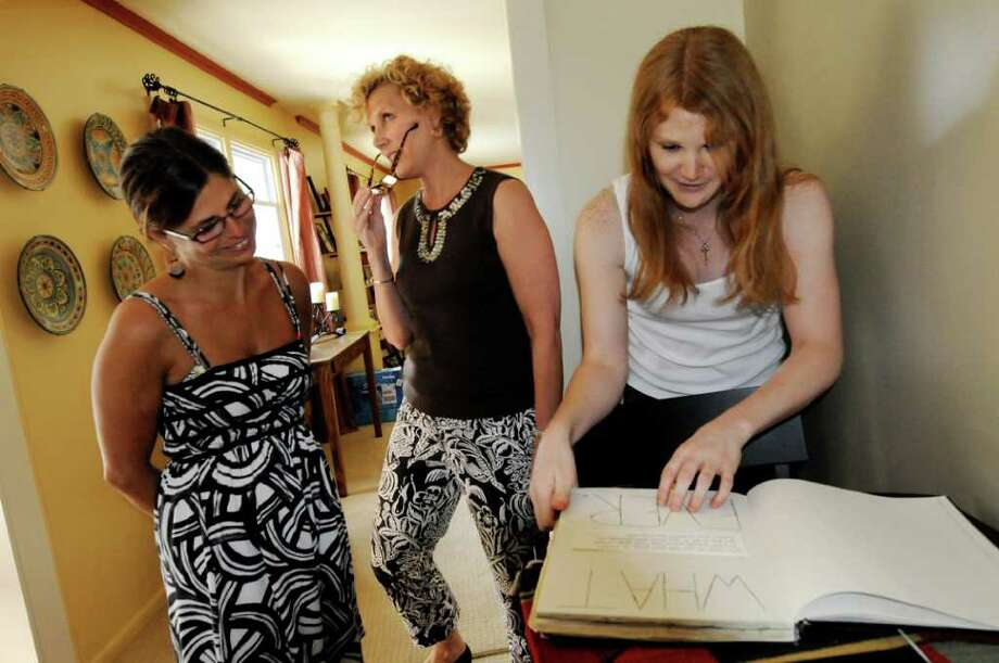 Drew Cordes, right, leafs through an old journal with her mother, Janet, center, and friend Melissa Mangino on Tuesday, June 21, 2011, at her parents' home in Glens Falls, N.Y. (Cindy Schultz / Times Union) Photo: Cindy Schultz, Albany Times Union