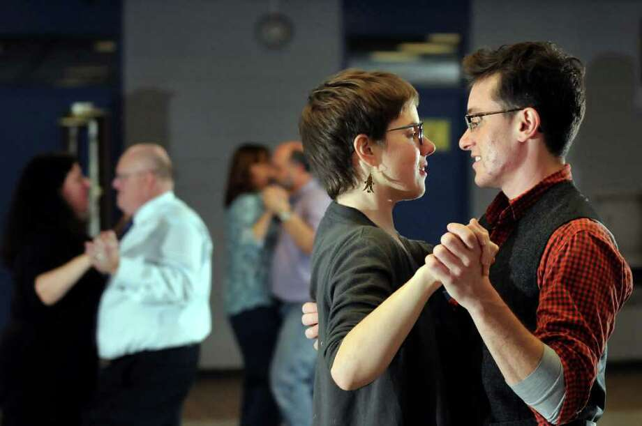 Christopher Argyros, right, learns dance steps with his girlfriend Laura Blosser during ballroom dance lessons on Thursday, Nov. 3, 2011, at Albany High in Albany, N.Y. Instructor Hershell Allen, left, watches their progress. (Cindy Schultz / Times Union) Photo: Cindy Schultz, Albany Times Union