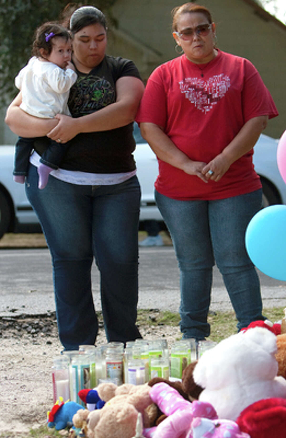 Cynthia Guzman holds her 10-month-old daughter Jolizzah Guzman, while her mom, Gloria Carranza, says a prayer in front of the home of victims that were shot outside their home Thursday, Dec. 1, 2011, in Bay City. Guzman stopped along with her mother, not pictured, because they know what it's like to know to lose a loved one.