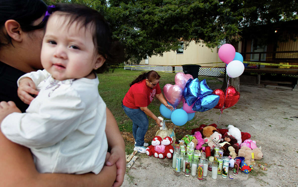 Cynthia Guzman holds her 10-month-old daughter Jolizzah Guzman, while her mom, Gloria Carranza places balloons in a vigil in front of the home of victims that were shot outside their home Thursday, Dec. 1, 2011, in Bay City. Guzman stopped along with her mother, not pictured, because they know what it's like to know to lose a loved one.