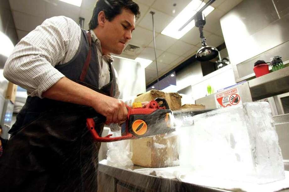 TASTE:  Drew's American Grill beverage manager  Rob Millican cuts large format ice on Monday Nov. 21, 2011.  HELEN L. MONTOYA/hmontoya@express-news.net Photo: HELEN L. MONTOYA, SAN ANTONIO EXPRESS-NEWS / hmontoya@express-news.net