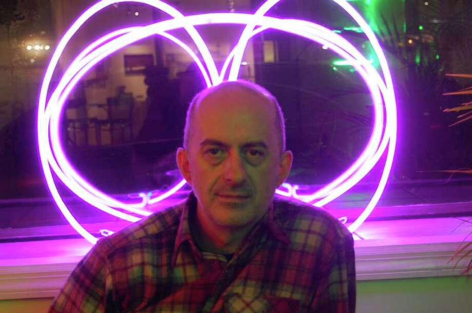 The artist Pietro Costa in front of one of his neon light sculptures at the Martinez Gallery in Troy. (Mike Hart)