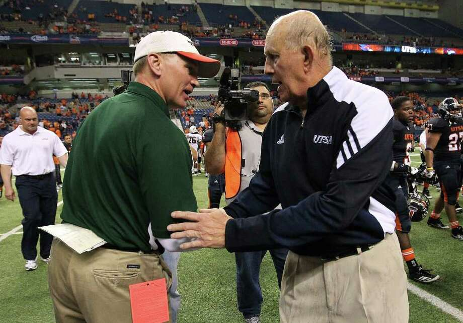 UTSA coach Larry Coker (right), shown shaking hands with Minot State coach Paul Rudolph after the Roadrunners' 49-7 victory on Nov. 19, can use the fact the Alamodome is UTSA's home field as a recruiting tool. But the school's other facilities are not top notch. Photo: Kin Man Hui, SAN ANTONIO EXPRESS-NEWS / San Antonio Express-News