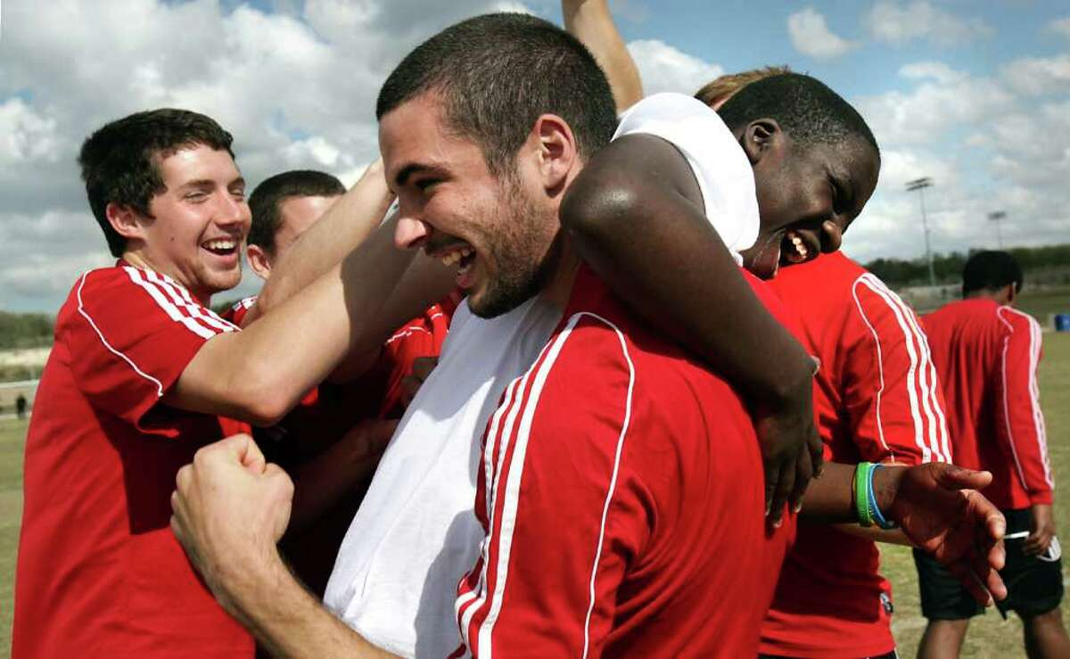 Travis Wall (center) captain of the Ohio Wesleyan University men's soccer team, hoists Bobby Todd on his shoulder as they and Matt Dodrill (left) celebrate a goal during a clinic held for 175 boys and girls from Special Olympics Texas Area 20 as part of the NCAA Division III soccer championships at the STAR Soccer Complex.