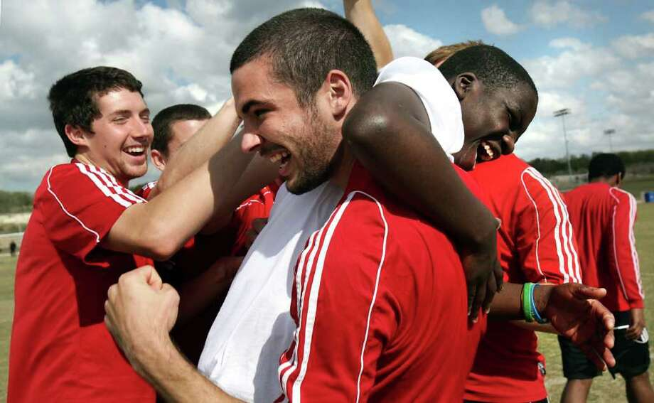 Travis Wall (center) captain of the Ohio Wesleyan University men's soccer team, hoists Bobby Todd on his shoulder as they and Matt Dodrill (left) celebrate a goal during a clinic held for 175 boys and girls from Special Olympics Texas Area 20 as part of the NCAA Division III soccer championships at the STAR Soccer Complex. Photo: BOB OWEN, SAN ANTONIO EXPRESS-NEWS / rowen@express-news.net
