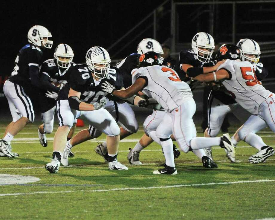 Staples offensive linemen Kyle Vaughn, 70, Chris Speer, 74, and Jack Gibson, 76, keep Ridgefield's defensive linemen at bay as quarterback Jack Massie, 16, hands the ball off to Jon Heil, 28 Tuesday. Heil rushed for 366 yards and the Wreckers had 547 yards of total offense in their 48-21 victory in the Class LL quarterfinals. Photo: April Book / Contributed Photo