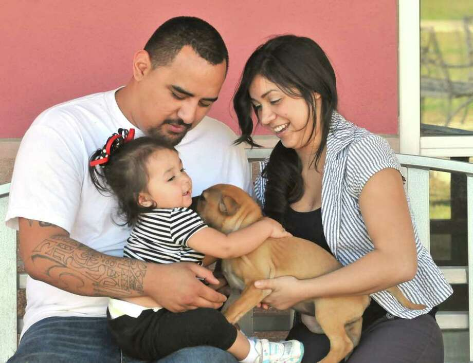 Noelani Gonzales, 1, and her parents play with their newly adopted dog from the San Antonio Animal Care Services kennel Thursday. Photo: FOR THE EXPRESS NEWS, ROBIN JERSTAD