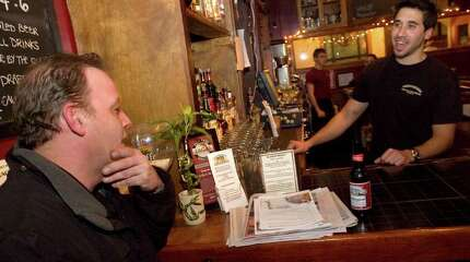 Luis Galbis, left, chats with bartender Christian Pace at Greenwood's Grille and Ale House in Bethel on Wednesday, Nov. 30, 2011. Galbis communtes on the train to his job as a mechanic at Riverbank Volkswagen in Stamford. He takes the 6 a.m. train and gets back to Bethel about 6 p.m. five days a week.