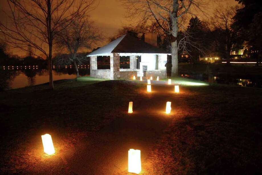 """In this December 2009 file photo, candles lead the way at Hamill Island at Binney Park in Old Greenwich as Boy Scout Troop 11 joined other residents to set up white lunch bags with candles for the Family Centers """"Hope Lights Lives"""" campaign. Two candle lightings will take place Saturday, Dec. 3, 2011 – one in Old Greenwich's Binney Park and the second at Tilley Pond in Darien. Both are scheduled for 5 p.m. A countywide lighting will take place at 5 p.m. Dec. 11, 2011. Photo: Contributed/John Ferris  Robben, Greenwich Time File"""