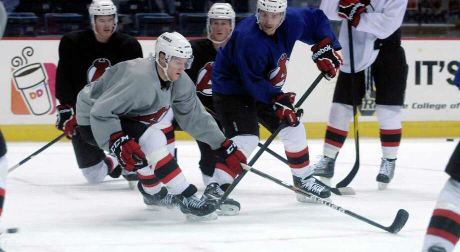 Brad Mills, left, plays defense as he practices with his Albany Devils teammates at the Times Union Center on Thursday, Dec. 1, 2011 in Albany, NY.  Mills was just sent down from New Jersey.  (Paul Buckowski / Times Union) Photo: Paul Buckowski / 10015628A