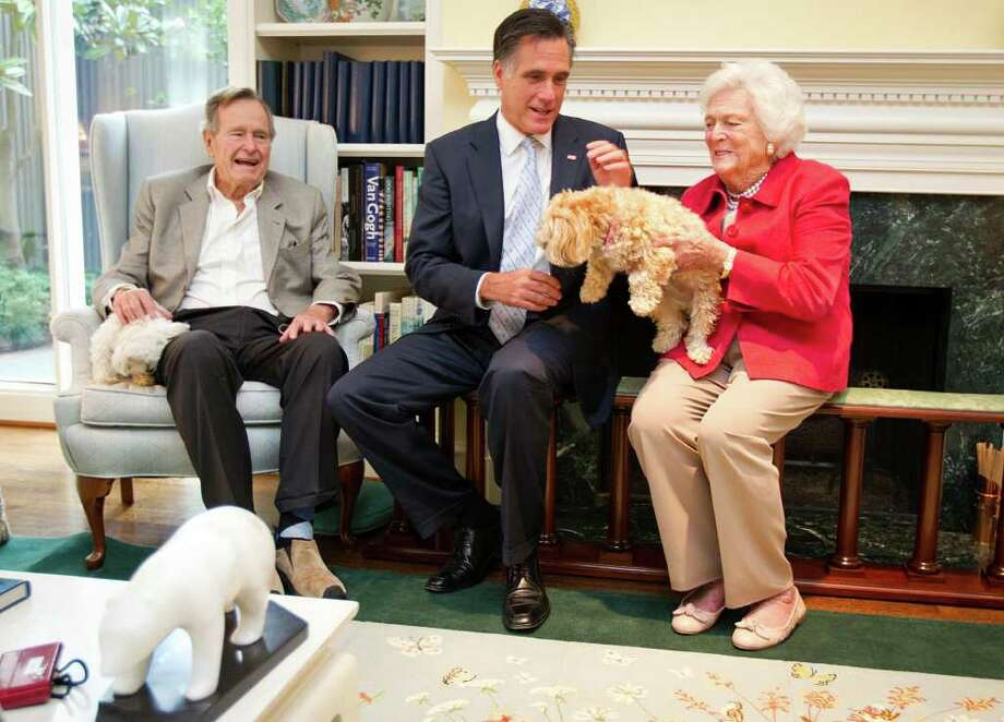 SMILEY N. POOL: CHRONICLE GIVEN PAWS:Former First Lady Barbara Bush offers her dog Bibi to GOP presidential candidate Mitt Romney while visiting with former President George H.W. Bush on Thursday. Photo: Smiley N. Pool / © 2011  Houston Chronicle