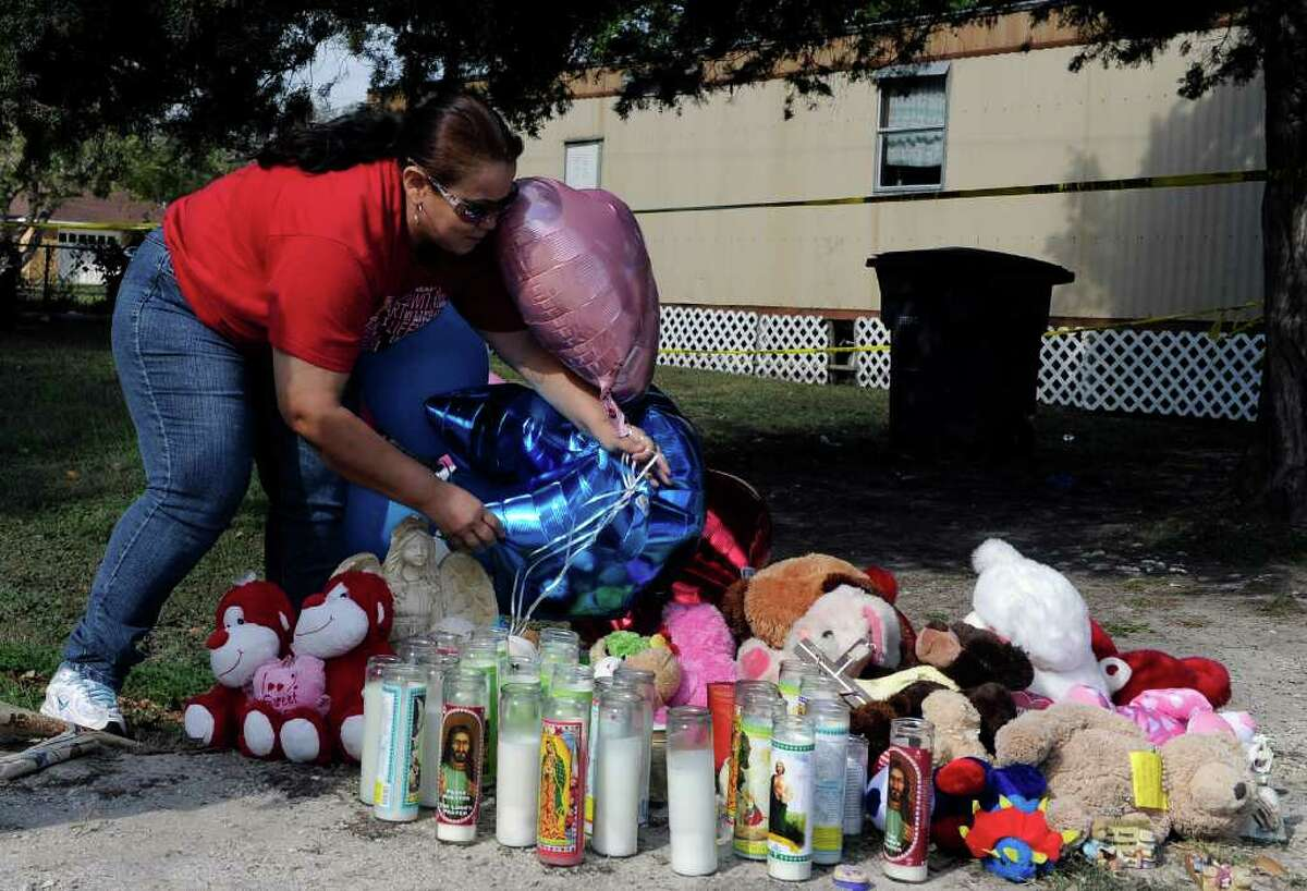 Gloria Carranza adds balloons to a makeshift memorial outside a trailer in Bay City, Texas, Thursday, Dec. 1, 2011, where a man shot four children and their mother on Wednesday before killing himself. (AP Photo/Pat Sullivan)