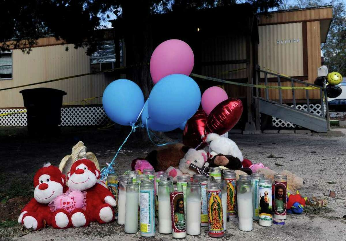 A makeshift memorial with balloons, stuffed animals and religious candles sits outside a trailer in Bay City, Texas, Thursday, Dec. 1, 2011, where a man shot four children and their mother on Wednesday before killing himself. (AP Photo/Pat Sullivan)