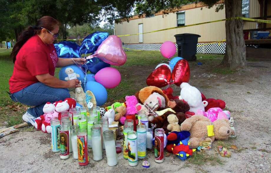 Gloria Carranza places balloons outside the home of five members of a family who died in Wednesday's incident. Photo: Cody Duty / © 2011 Houston Chronicle