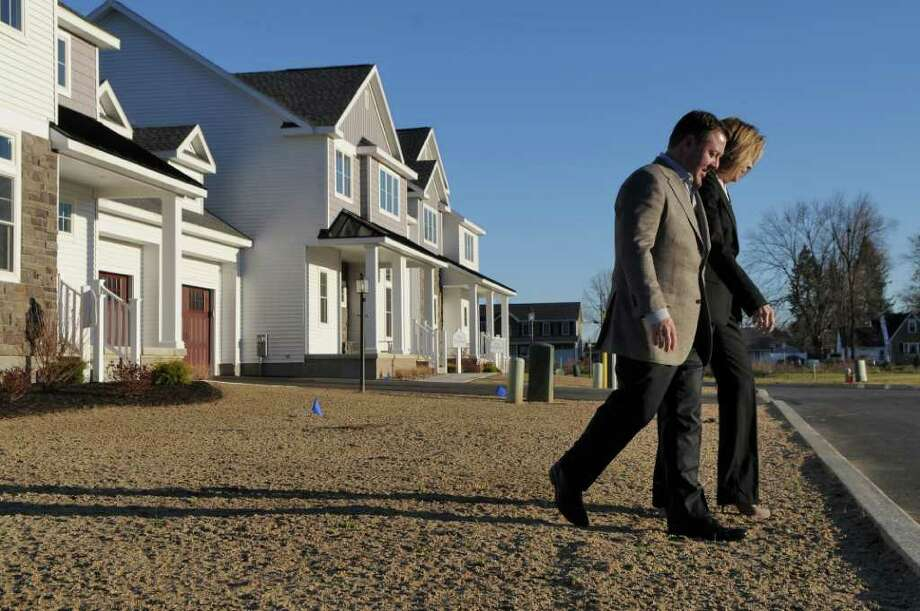 Frank Barbera, Vice President of Parkside at the Crossings, Inc., left, walks with Patricia Whelan outside models of the new condominium project under construction off Sand Creek Road on Thursday Dec. 1, 2011 in Colonie, NY.   Colonie saw a $32 million jump in assessments last year, due largely to housing development. (Philip Kamrass / Times Union ) Photo: Philip Kamrass / 00015573A