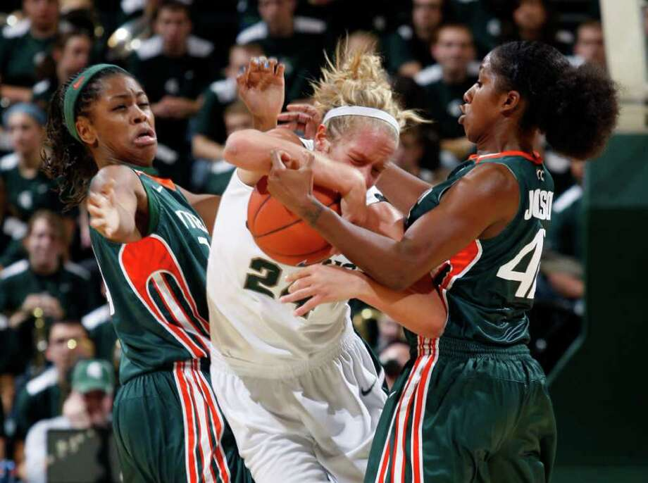 Miami's Sylvia Bullock, left, and Shenise Johnson, right, pressure Michigan State's Courtney Schiffauer, center, during the second half of an NCAA college basketball game, Thursday, Dec. 1, 2011, in East Lansing, Mich. Miami won 76-60. Photo: Al Goldis