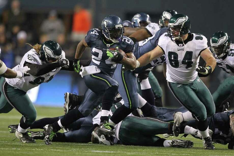 SEATTLE - DECEMBER 01:  Running back Marshawn Lynch #24 of the Seattle Seahawks rushes against Trevor Laws #91 and Derek Landri #94 of the Philadelphia Eagles at CenturyLink Field on December 1, 2011 in Seattle, Washington. Photo: Otto Greule Jr, Getty Images / 2011 Getty Images