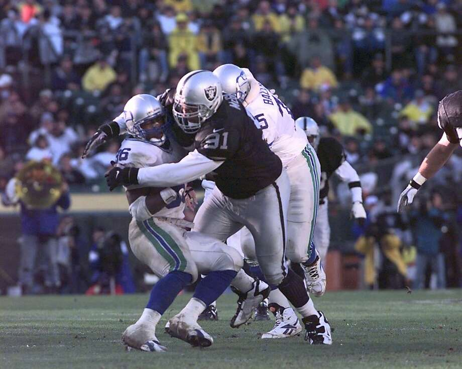 RAIDERS MCGLOCKTON/C/22DEC96/SP/CS - The Raiders defensive tackle Chester McGlockton (91) buries the Seahawks running back Lamar Smith (36).  SAN FRANCISCO CHRONICLE PHOTO BY CHRIS STEWART Ran on: 02-09-2007 Former Raiders lineman Chester McGlockton (center) would like to open a Fatburger in Oakland's Grand Lake neighborhood. Ran on: 02-09-2007 Former Raiders lineman Chester McGlockton (center) would like to open a Fatburger in Oakland's Grand Lake neighborhood. Photo: Chris Stewart, The Chronicle