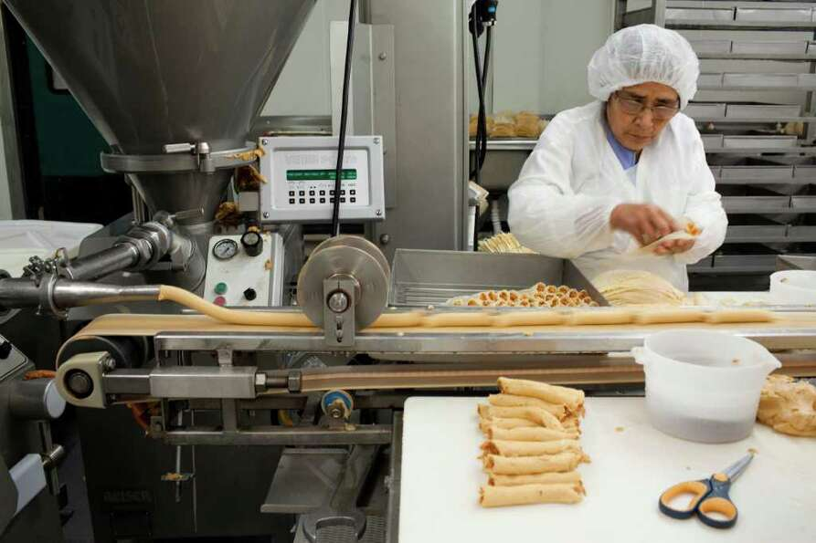 Gabby Martienez, who has worked at Alamo Tamales for 27 years, is one of the workers cranking out 12