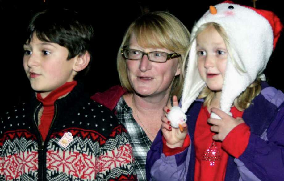 SPECTRUM/Thomas Piller, 7, and his friend, Carly Lynch, 6, of New Milford team up, with his mom, Carri Piller, to sing Christmas carols during the Village Center Organization's Festival of Lights celebration on the Village Green. Nov. 26, 2011 Photo: Walter Kidd